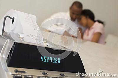 Machine de reçu de dépenses avec des couples à l arrière-plan
