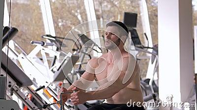 Macht opleiding, bodybuildermannetje met naakt-chested het doen spier de bouwtraining op tractiesimulator terwijl het werken aan stock footage