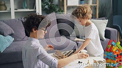 Macierzysty i mały syn umieszcza szachowych kawałki na chessboard bawić się w domu przy stołem zbiory