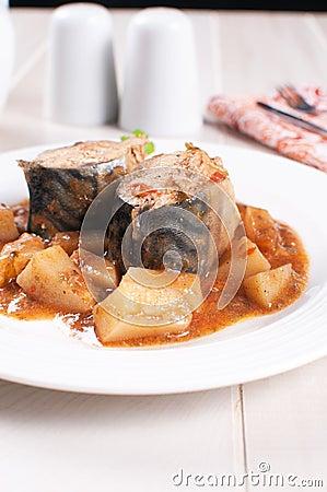 Mackerel pieces closeup with potato and tomato