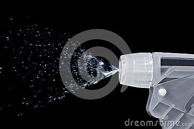 Macro of a bottle nozzle spraying water