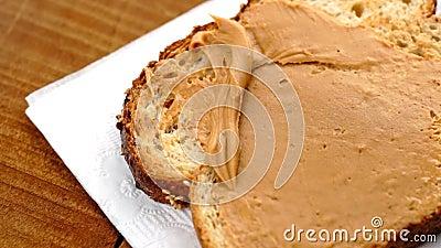 Macro del movimento lento di spandere burro di arachidi cremoso su pane tostato a basso contenuto di carboidrati archivi video