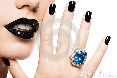 Macro shot of a woman s lips and nails painted bright color blac