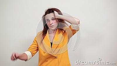 Mad jonge vrouw in een gele jas die hand op haar hoofd houdt en boos lijkt stock videobeelden