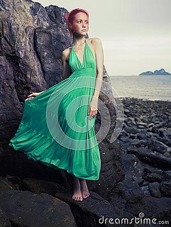 Madame dans la robe verte sur le bord de la mer