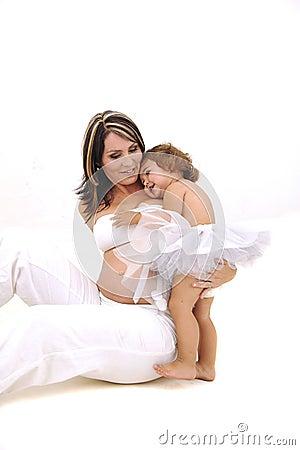 Madre con las tetas al aire embarazada que juega con su niño
