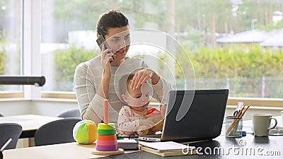 Madre con un bambino che lavora sul portatile in ufficio stock footage