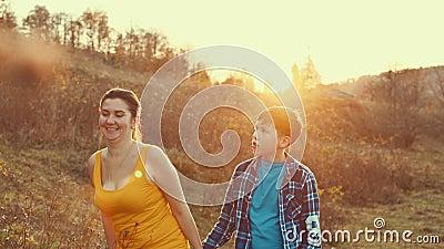 Madre e figlio camminano insieme nell'erba del prato con una bella luce del tramonto, sentendo l'amore per la vita familiare stock footage