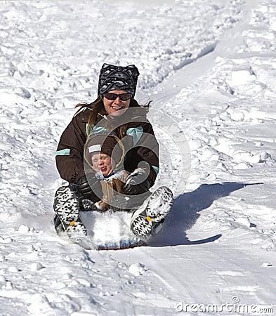 Madre e figlio divertendosi sulla collina della slitta