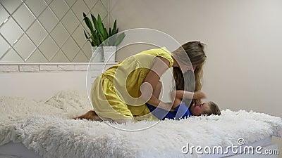 Madre e figlio si divertono sul letto, la donna fa il solletico al ragazzo e ride archivi video