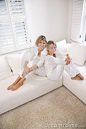 Madre e hija adolescente que se relajan en el sofá blanco