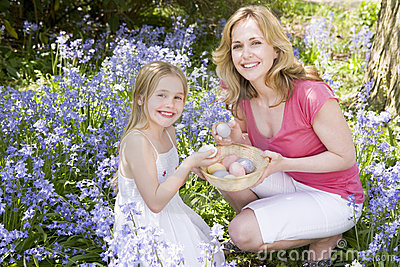 Madre e hija en Pascua que busca los huevos