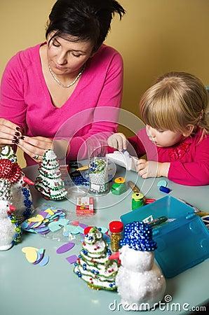 Madre e hija que hacen decoraciones de la Navidad