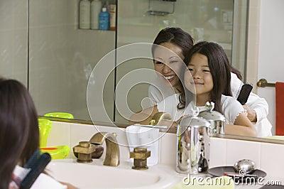 Madre e hija que miran el espejo de la reflexión