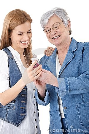 Madre e hija que miran las fotos en móvil