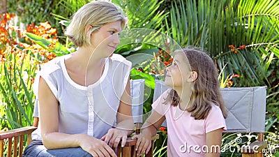 Madre e hija que se sientan en sillas y hablar de jardín metrajes