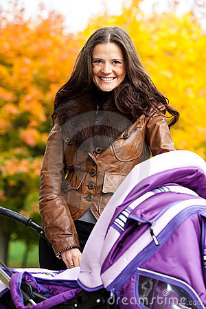 Madre feliz con el cochecito de niño