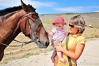 Madre habituating su bebé con el caballo