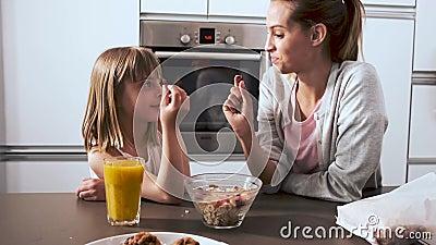 Madre hermosa y su hija que toman y que comen los cereales del cuenco en la cocina en casa almacen de metraje de vídeo