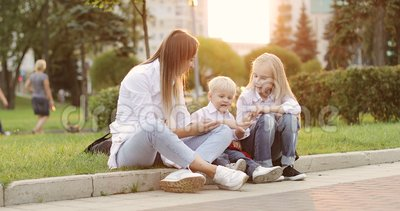 Madre joven con el muchacho rubio y la muchacha que se divierten en el parque del verano almacen de metraje de vídeo