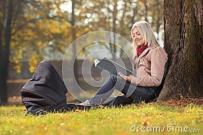 Madre joven que se sienta en un parque y que lee una historia a su bebé