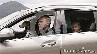 Madre, padre, cane del cane da lepre e del figlio che si siedono nell'automobile, cinghie di fissaggio e movimento fuori al viagg archivi video