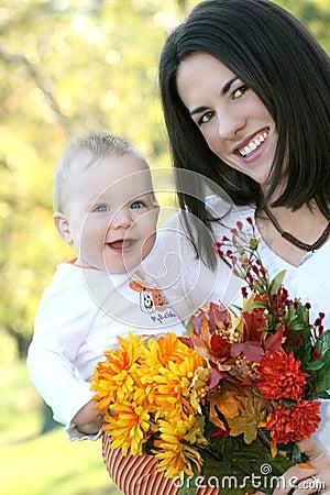 Madre y bebé con las flores - tema de la caída