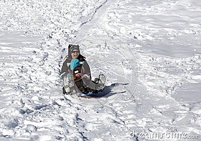Madre y niños que se divierten en la colina del trineo