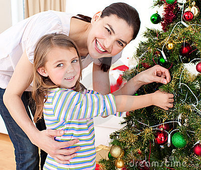 Madre y su muchacha que adornan un árbol de navidad