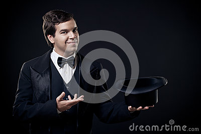 Magician showing tricks with top hat isolated on dark