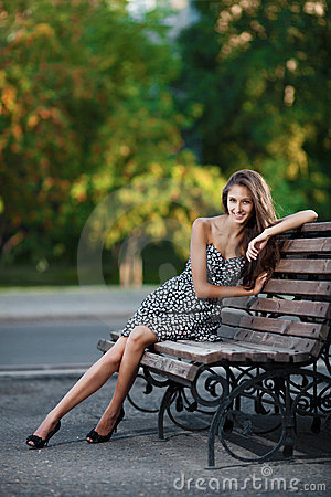 Magnificent brunette sits on bench