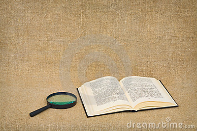 Magnifier and open book lie against a brown canvas