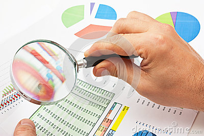 Magnifying glass in hand and paper