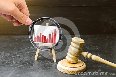 Magnifying glass is looking at the stand information graphics and a wooden hammer of a judge. Rising crime. Improving efficiency Stock Photo