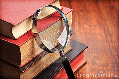 Magnifying glass with old books