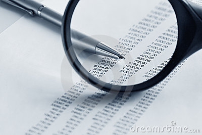 Magnifying glass  and pen over financial report