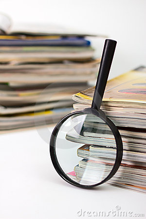 Magnifying lens  and stack of magazines