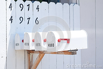 Mailboxes in front of white fence