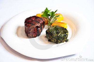 Main course beef with spinach white plate