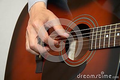 Main de guitariste, doigts jouant la guitare acoustique