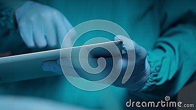 Main enfilée de gants tenant le comprimé Technologie diagnostique Comprimé de prise de mains de chirurgien clips vidéos