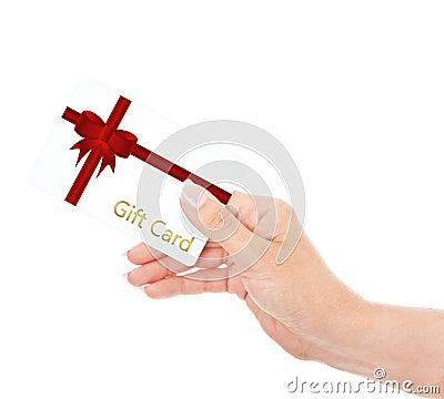 Main jugeant la carte cadeaux d isolement au-dessus du blanc