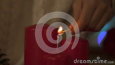 Mains d'enfant allumant des bougies avec le match, sécurité incendie au temps de Noël, plan rapproché clips vidéos