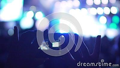 Mains femelles prenant des photos au téléphone au concert, utilisant l'instrument pour économiser des souvenirs clips vidéos