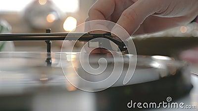 Mains masculines mettant une aiguille sur un disque clips vidéos