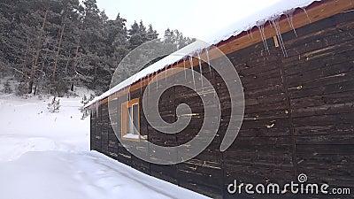 Maison en bois en hiver avec des glaçons banque de vidéos
