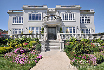 Majestic two story mansion with shrubs in yard