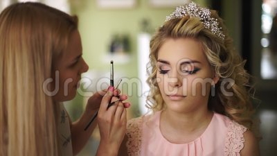 Make-up artist paints the face of the bride, in a beautiful salon. Professional makeup for woman with healthy young face. Skin. Beauty salon. Visage and make up stock video