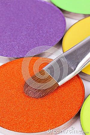Make-up brush on orange eye shadows palette