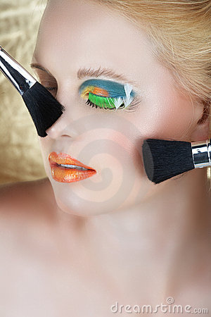 Make-up brushes on blond woman